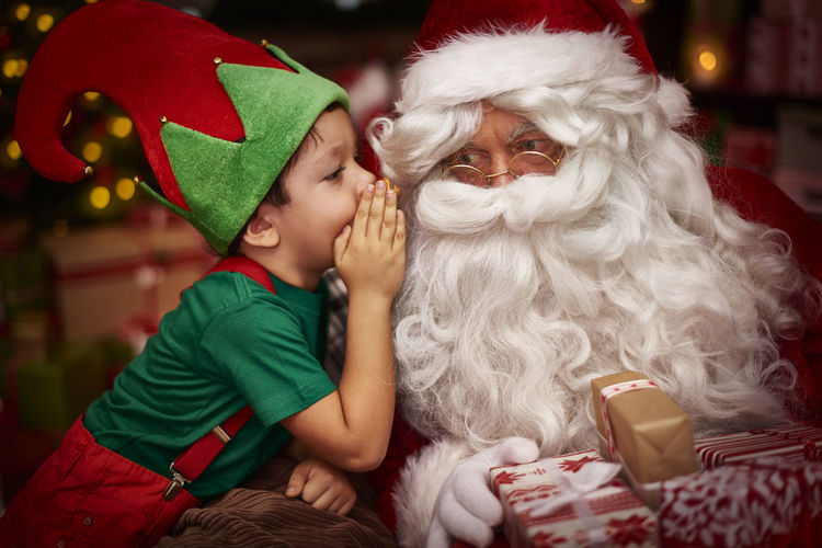 Side View Of Boy With Santa Claus Sitting At Home