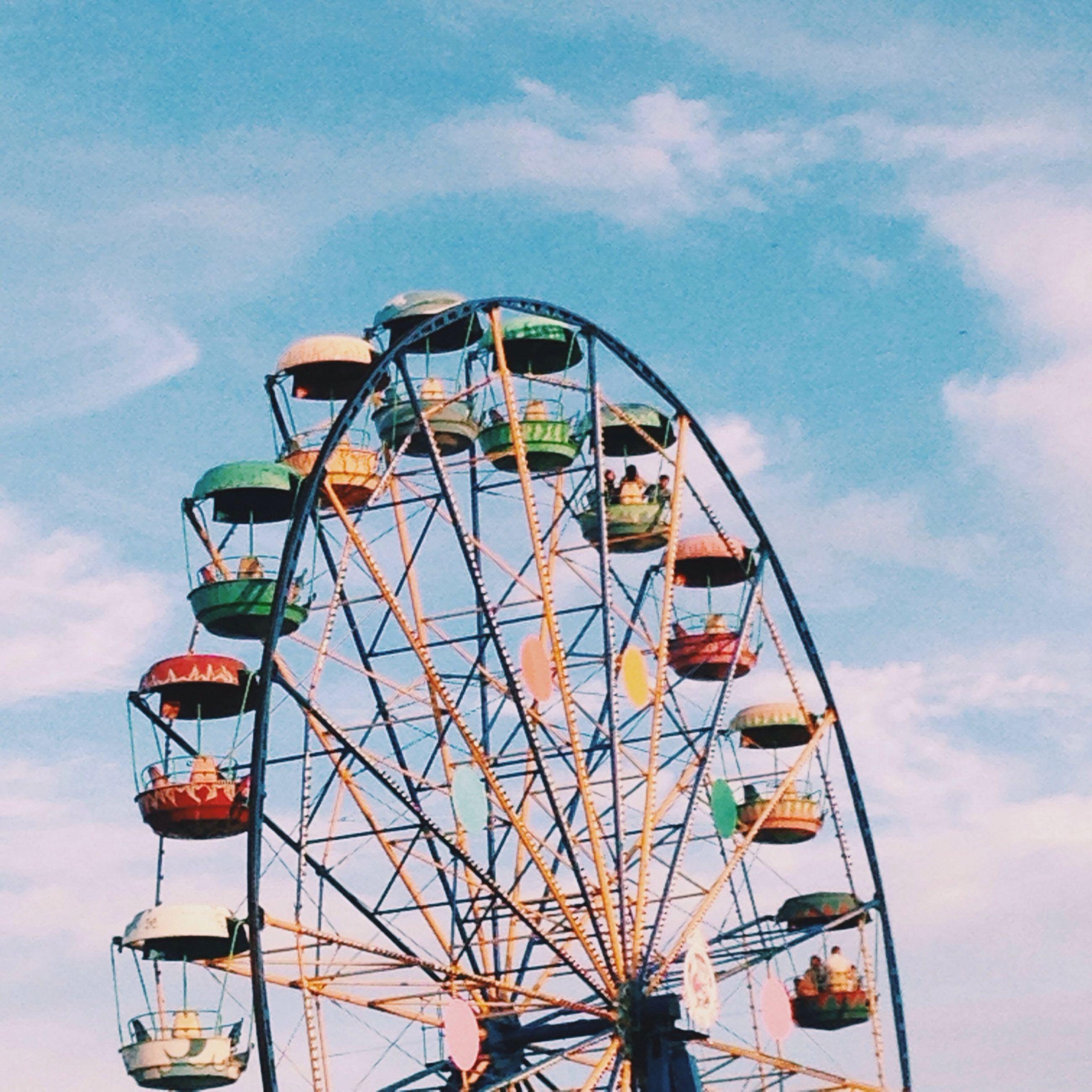 amusement park, amusement park ride, ferris wheel, sky, low angle view, arts culture and entertainment, cloud - sky, transportation, mode of transport, built structure, cloud, day, outdoors, cloudy, leisure activity, multi colored, wheel, architecture, fun, metal