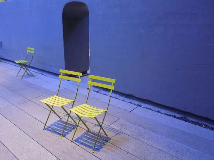 High angle view of yellow chairs on sidewalk against wall