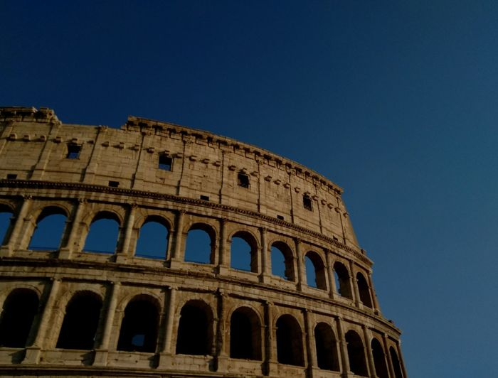 Low angle view of coliseum against clear blue sky