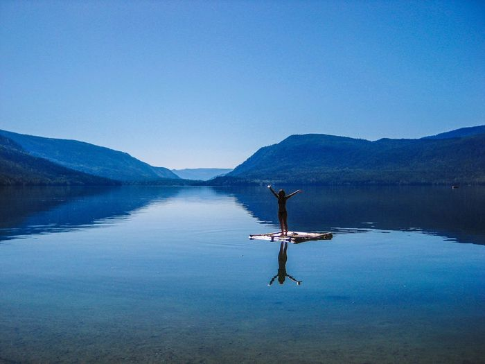 Woman with arms raised standing on wooden raft in lake against clear blue sky
