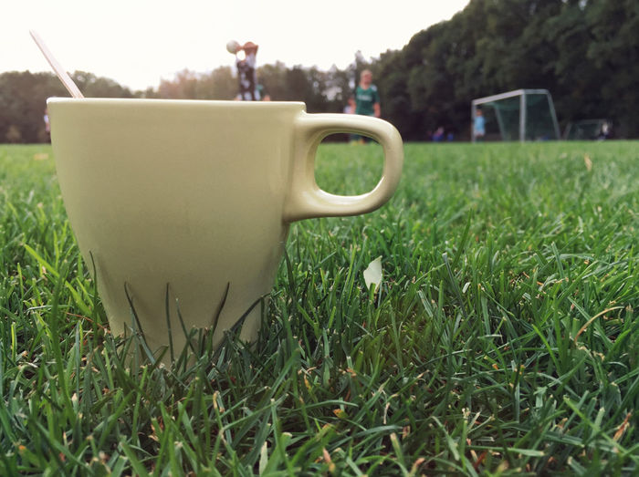Close-up of coffee cup on grass