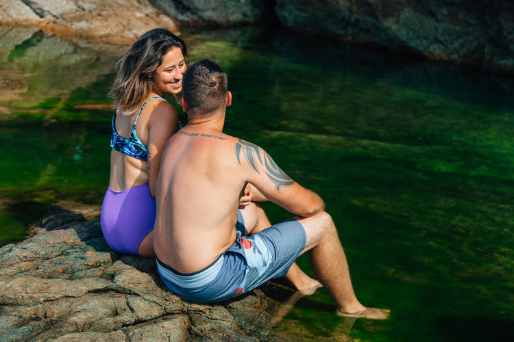 Two People Togetherness Lifestyles Couple - Relationship Leisure Activity Men Sitting Adult Heterosexual Couple Young Men Young Adult Nature Real People Women Love Shirtless People Bonding Water Positive Emotion Outdoors