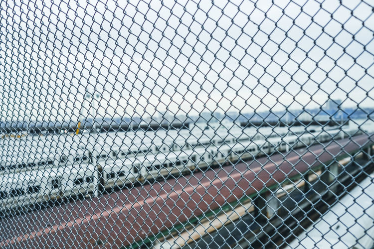 Close-Up Of Trains Seen Through Chainlink Fence Against Clear Sky