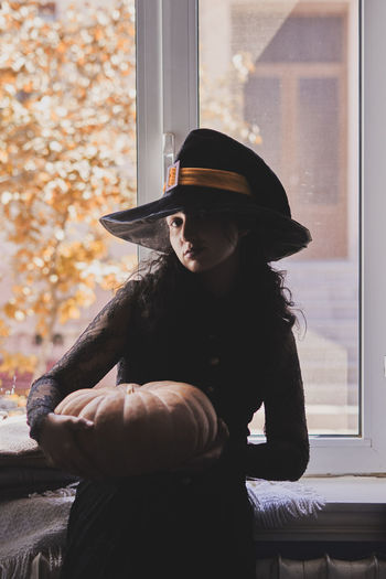 Halloween lady wearing witch cup. a woman in witch hat and halloween pumpkin near the windows