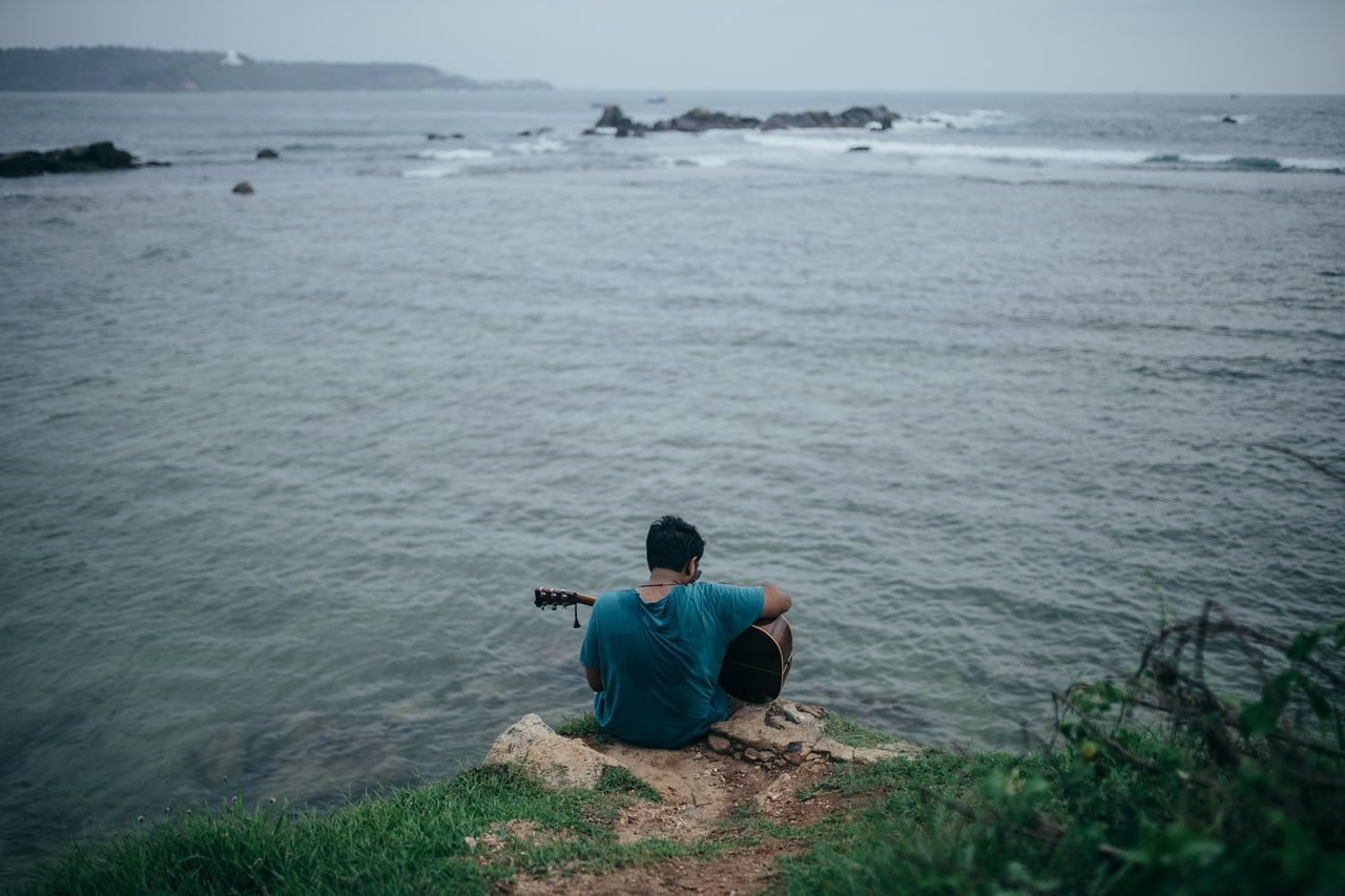 High Angle View Of Man Playing Guitar While Sitting On Rock By Sea