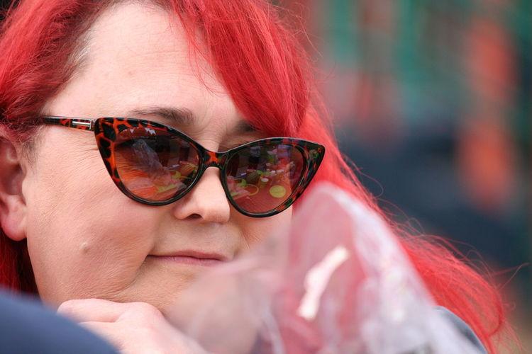 Close-up of mature redhead woman wearing sunglasses