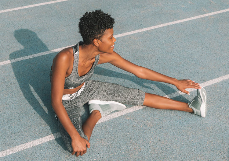 High angle view of smiling woman stretching leg on sports track