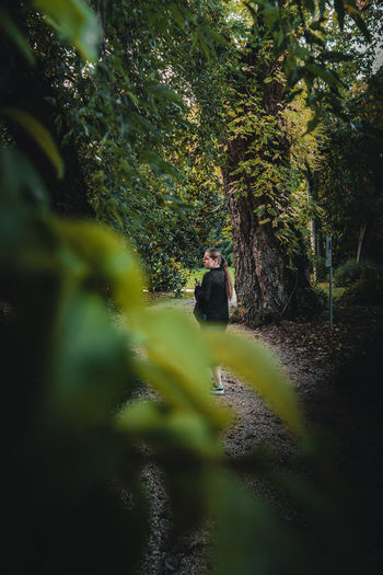 Man sitting by tree in forest