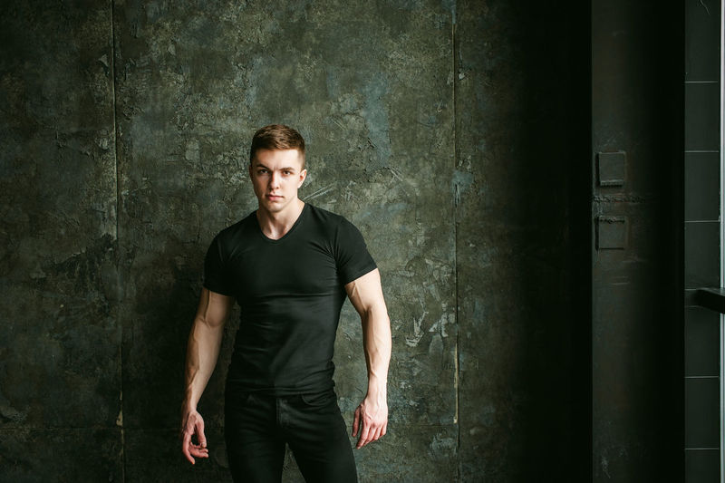 Portrait of muscular man standing by wall