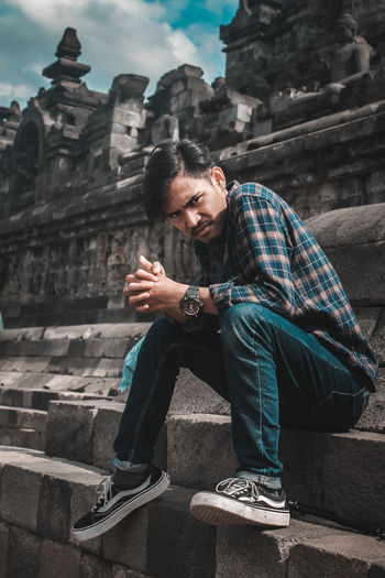 Young man sitting outside temple