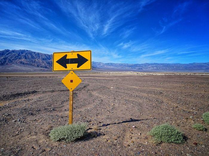 Arrow sign on road against sky
