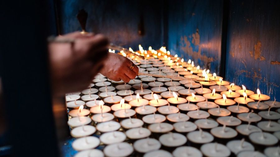 Cropped image of people burning incense with tea light candles at temple