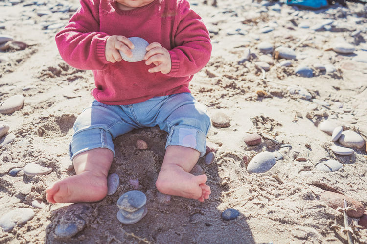 Low section of child playing on sand