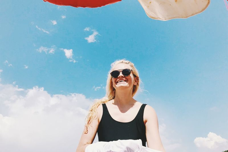 Cheerful woman wearing sunglasses standing against sky during sunny day