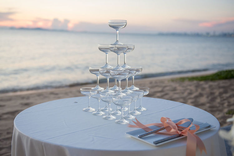 Close-Up Of Stack Of Champagne Glasses On Wedding Table At Beach