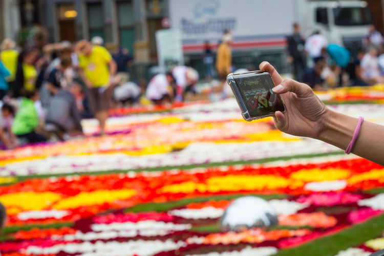 Flower carpet in Brussels 2018 Moments Of Happiness Human Hand Real People Hand Photography Themes Photographing Smart Phone Technology Wireless Technology Human Body Part One Person Communication Market Women City Incidental People Mobile Phone Activity Portable Information Device Day Outdoors Retail Display Flower Carpet Brussels