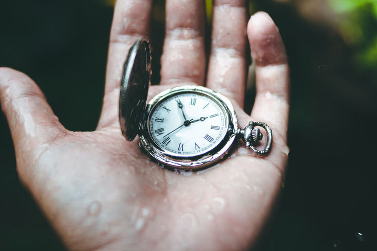 Close-up of human hand holding clock