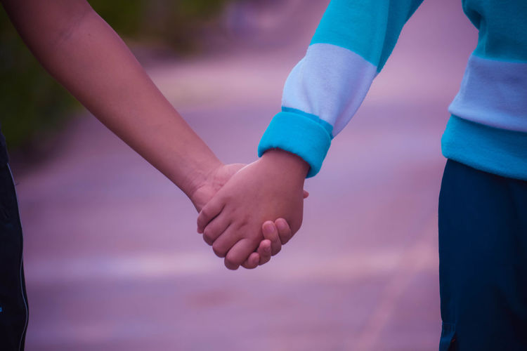 Close-up of friends holding hands