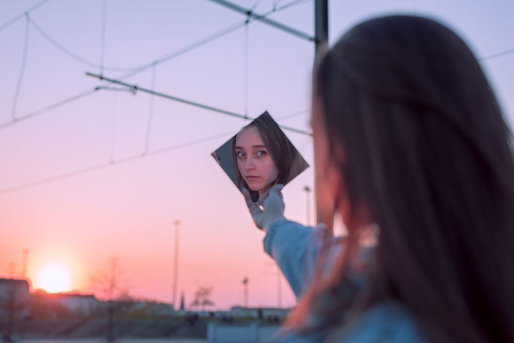 Woman holding mirror against sky during sunset