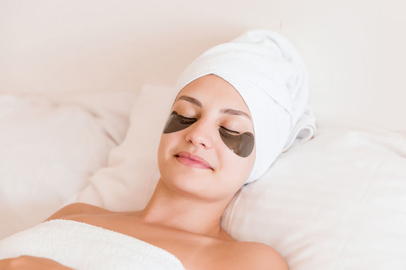 Smiling young woman with under eye patches lying on bed at spa