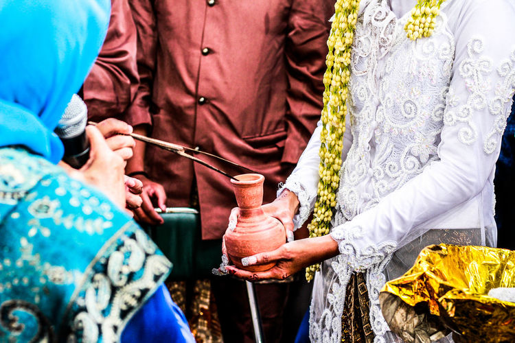 Midsection of bride and bridegroom during wedding ceremony