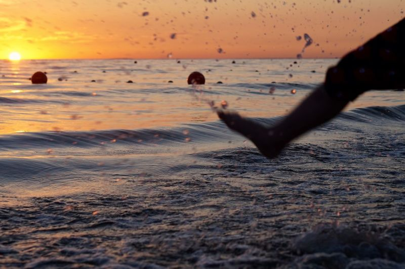 Low section of person splashing water at beach during sunset