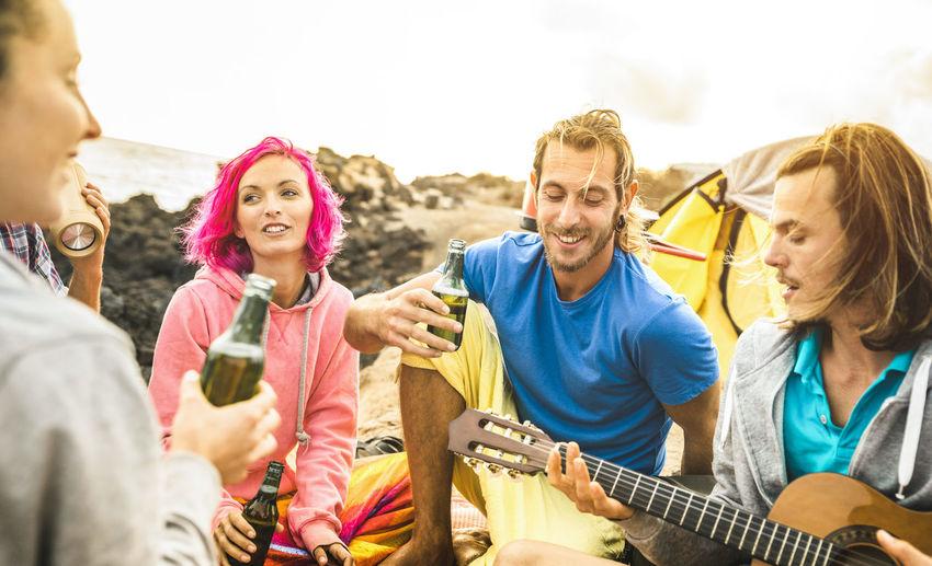 Male and female friends enjoying music at beach