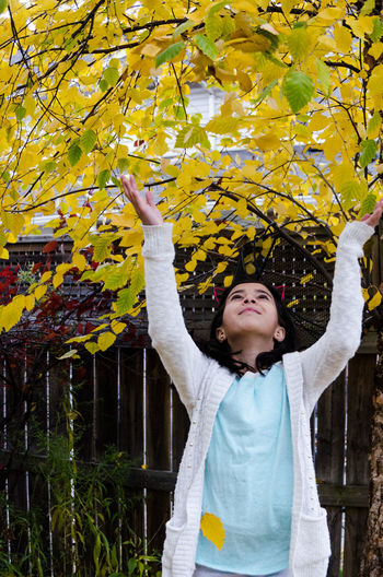 Smiling girl with arms raised touching with tree leaves during autumn