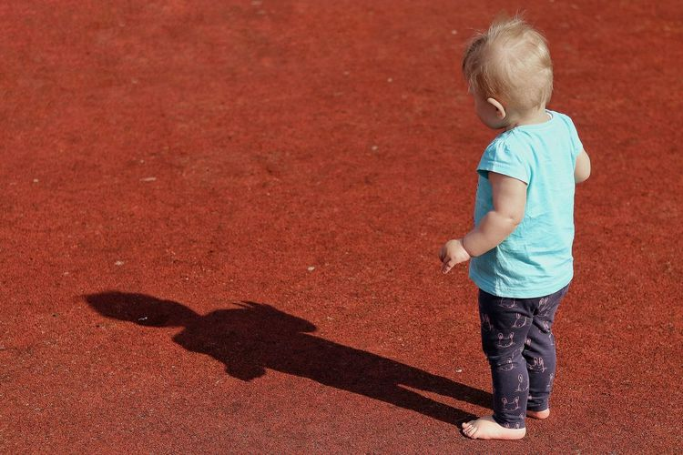 High angle view of girl standing on footpath with shadow