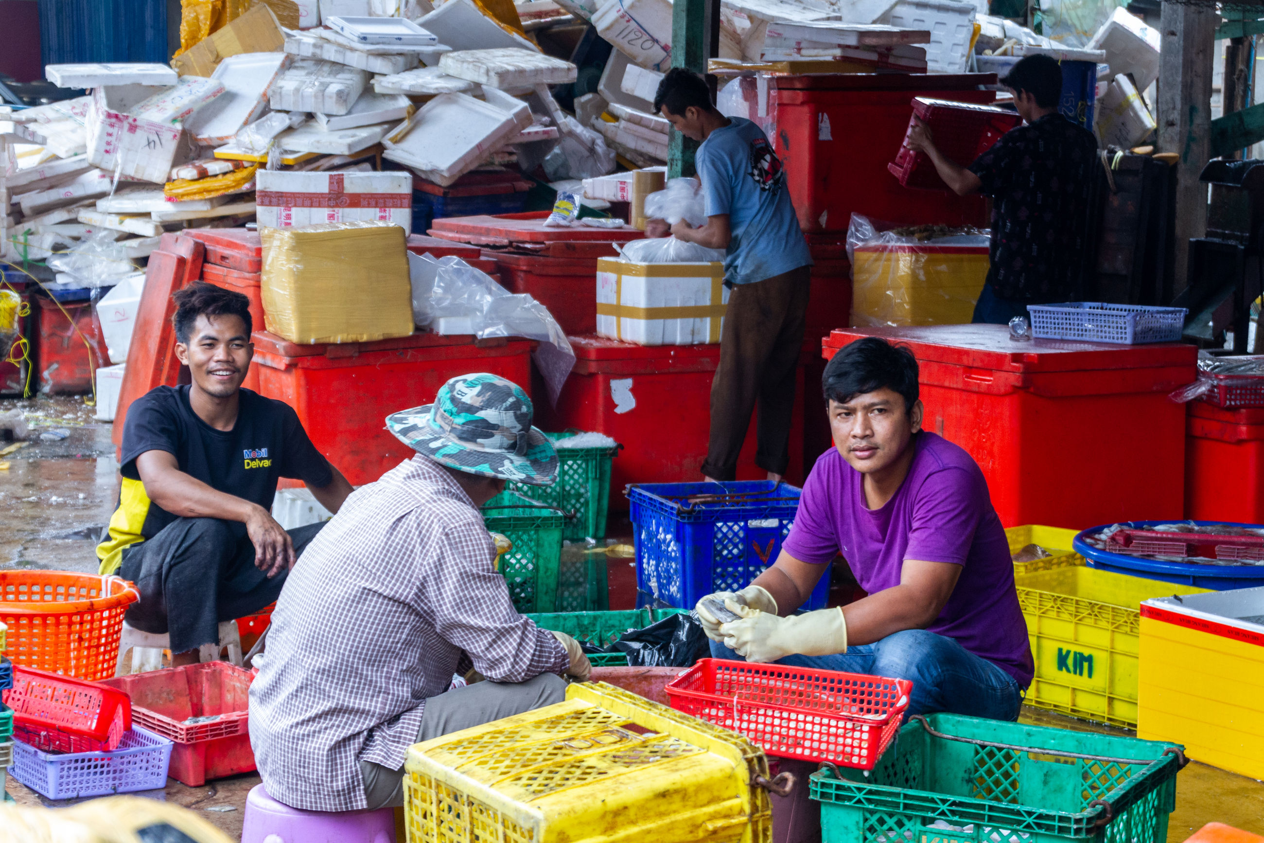market, retail, women, market stall, sitting, small business, for sale, business, real people, container, casual clothing, people, group of people, adult, front view, men, large group of objects, portrait, choice, three quarter length, buying, sale, retail display