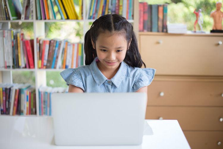 Girl using laptop while sitting at desk
