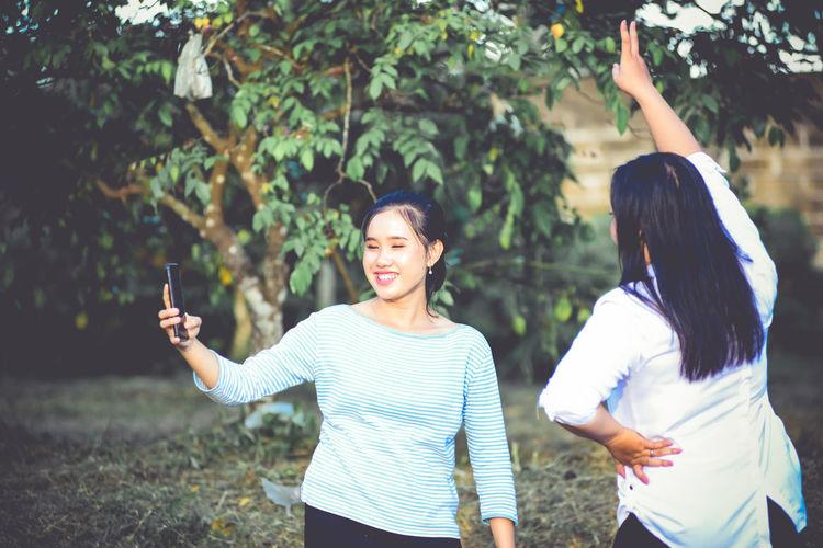 Friends standing against plants