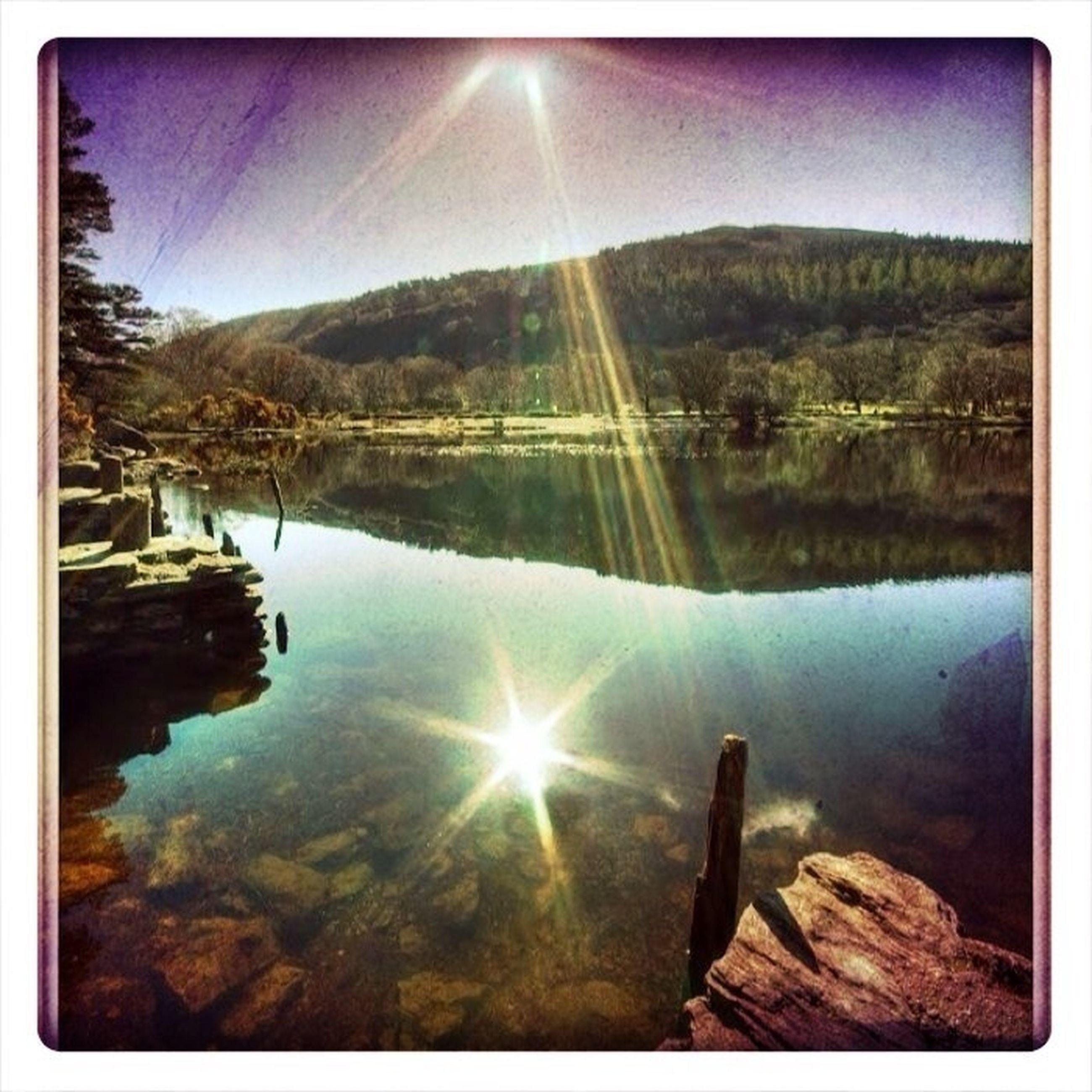 water, reflection, transfer print, tranquil scene, tranquility, lake, scenics, sun, beauty in nature, sunbeam, nature, sunlight, auto post production filter, sky, lens flare, river, idyllic, tree, mountain, non-urban scene