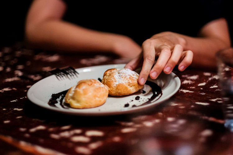 Tempting to eat the cream puff Food And Drink Food Human Hand Plate Indoors  One Person Hand Sweet Food Freshness Table Human Body Part Selective Focus Baked Ready-to-eat Indulgence Sweet Dessert Close-up Temptation Finger