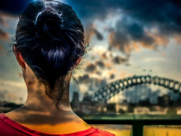 Rear view of young woman watching bridge against cloudy sky