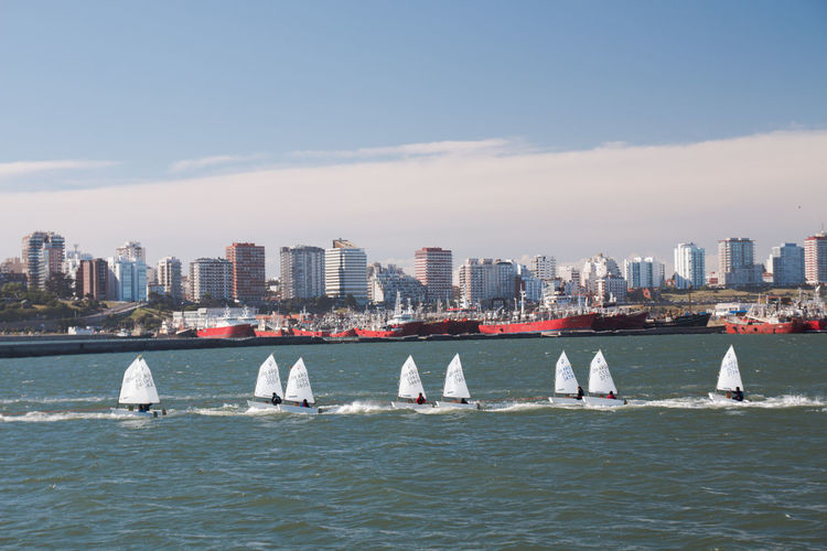 Sailboats in sea by buildings against sky