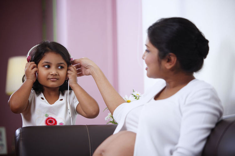 Girl Listening Music With Pregnant Mother While Sitting On Sofa At Home