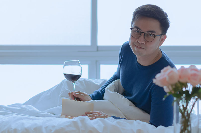 Mid adult man holding drink sitting on table