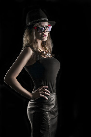 Studio photography. Three quarters portrait of a woman in stylish clothes and a hat and a pair of glasses. Shooting with black background. Black Background Body & Fitness Fashion Glasses Hat People Watching Portrait Of A Woman Portraits Studio Woman Black Blond Hair Body Curves  One Person One Woman Only One Young Woman Only People people and places People Photography Portrait Portrait Photography Real People Spy Studio Shot Three Quarter Length