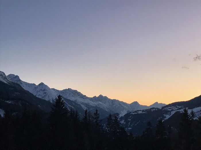 Scenic view of snowcapped mountains against clear sky during sunset