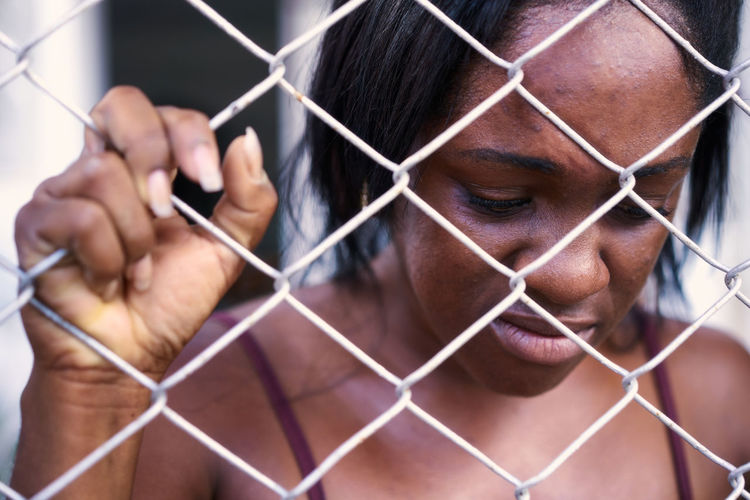 Shirtless sad woman holding chainlink fence