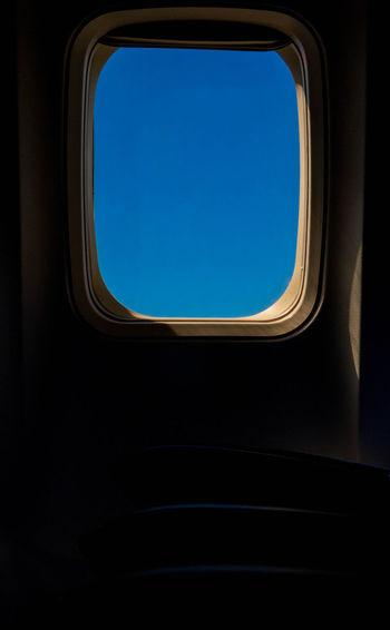 Clear blue sky through airplane window