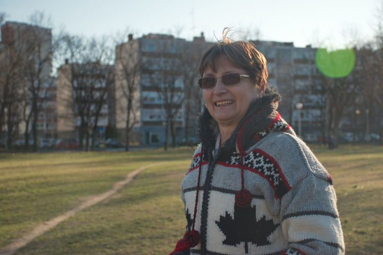 Smiling Portrait One Person Happiness Real People Lifestyles Architecture Leisure Activity Building Exterior Glasses Waist Up Focus On Foreground Looking At Camera Nature Standing Clothing Built Structure Warm Clothing Fashion Outdoors Park Grass Green Wool Mature Adult