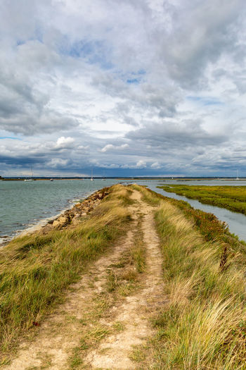 A pathway near the sea, on the Isle of Wight Cloud - Sky Sky Grass Tranquility Tranquil Scene Scenics - Nature Beauty In Nature Water Plant Nature Land No People Day Environment The Way Forward Direction Sea Landscape Non-urban Scene Outdoors Marram Grass Trail Long Pattern Marshland