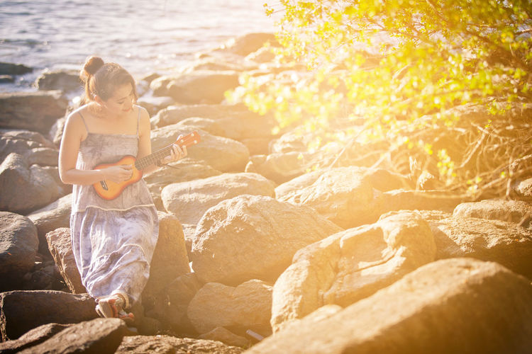 Rock One Person Land Beach Sitting Rock - Object Water Sunlight Full Length Nature Childhood Day Leisure Activity Sea Holiday Child Vacations Outdoors Lens Flare Innocence Music Ukulele Guitar Relaxing Thailand