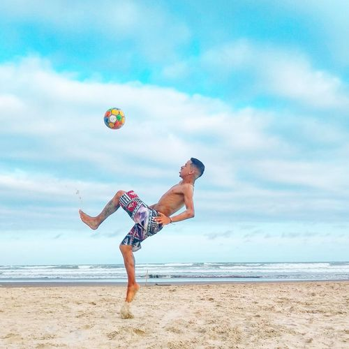 Full length of shirtless man playing soccer at beach against sky