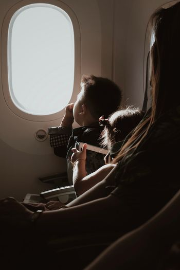 Side view of girl sitting in airplane