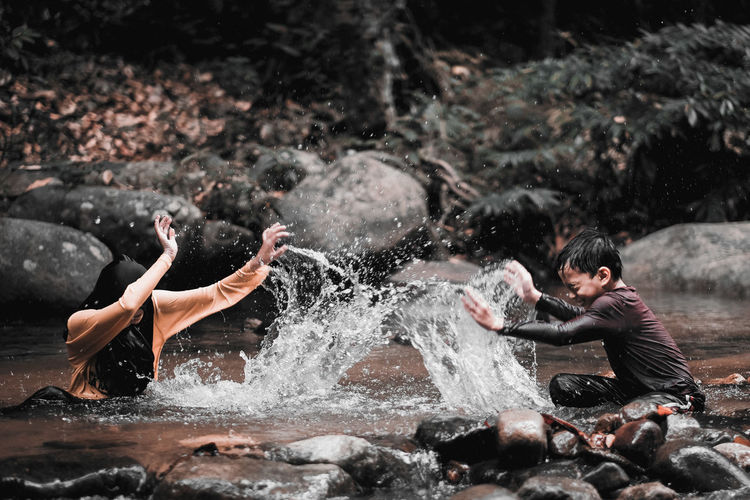Cheerful siblings splashing water in river