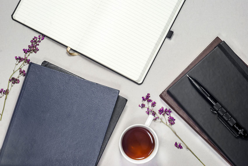 Blank Book Cup Desk Drink Flower Flowering Plant Furniture High Angle View Indoors  Mug No People Note Pad Paper Pen Plant Publication Refreshment Still Life Table Technology Wireless Technology Writing Instrument